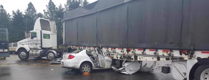 This image shows a car destroyed under a semi truck