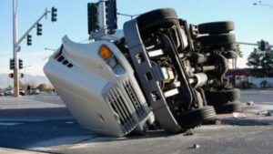 This image shows a semi-truck overturned on a highway